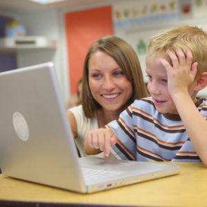 teacher helping a child on a computer