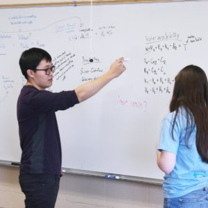 Two students doing math at a whiteboard