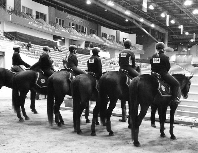 students riding horses in a large arena
