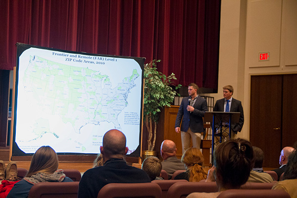 Students giving a presentation in an auditorium