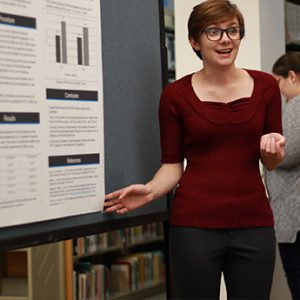 Student making a presentation at a poster