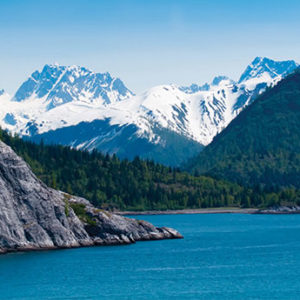 Ocean, forest and snowcapped mountains