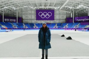 Student standing on an Olympic ice rink