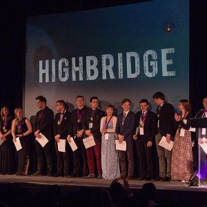Students standing on stage holding awards