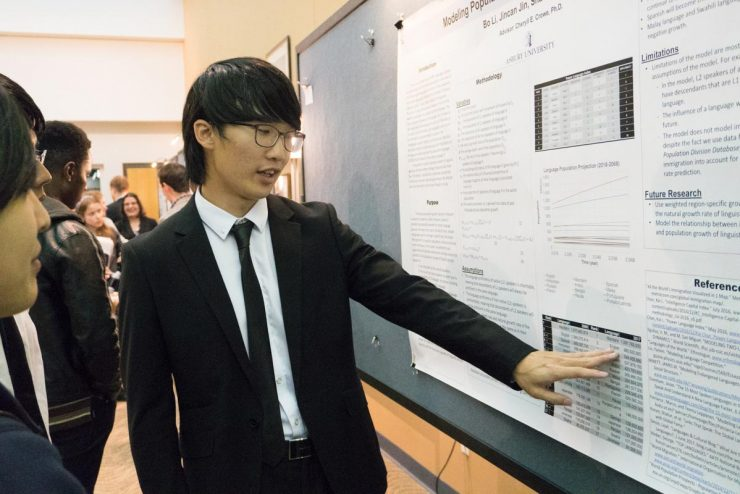 student delivering a poster presentation