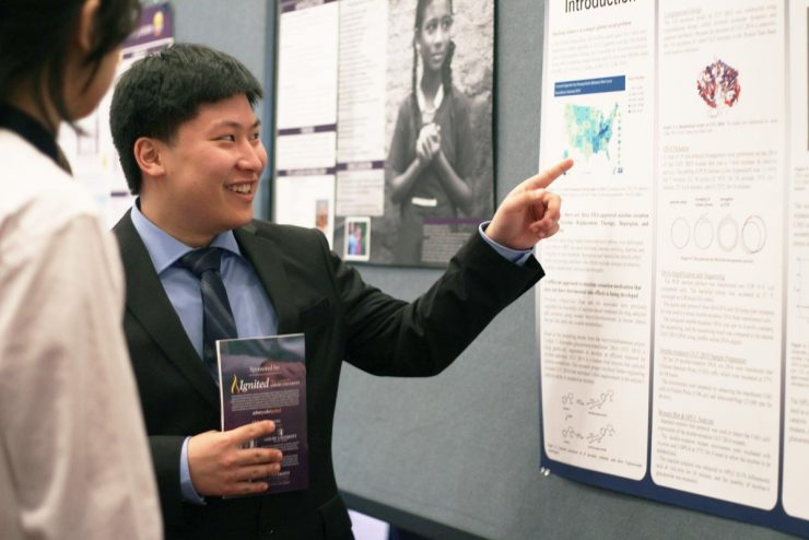 Asian student giving a poster presentation