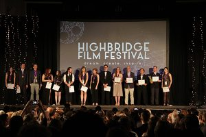 Students standing on stage with awards