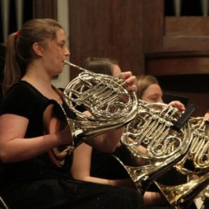 Students playing brass instruments in orchestra