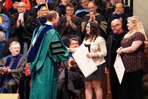 student receiving an award on stage during a ceremony