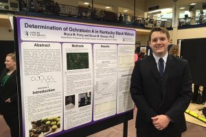 Student standing in front of a presentation poster