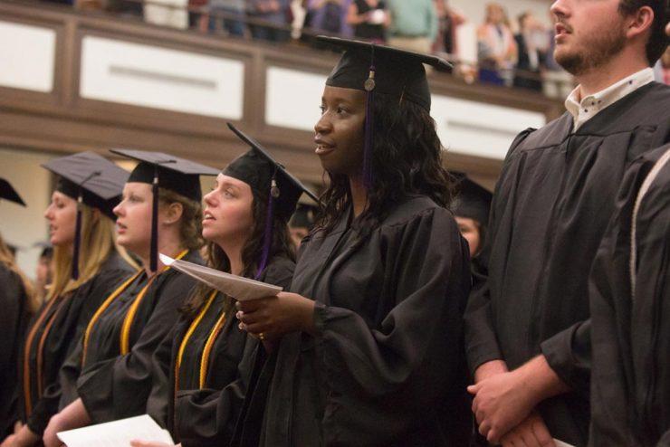 graduate in cap and gown standing in Hughes Auditorium