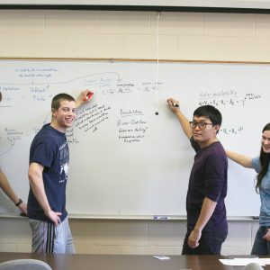 math students writing on a whiteboard