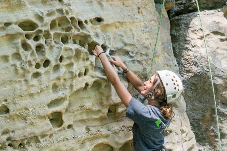 student climbing a rock face