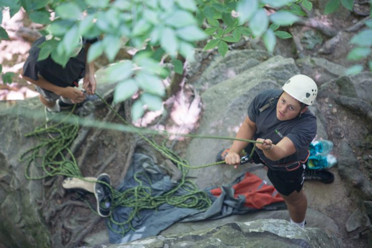 student belaying a rock climber