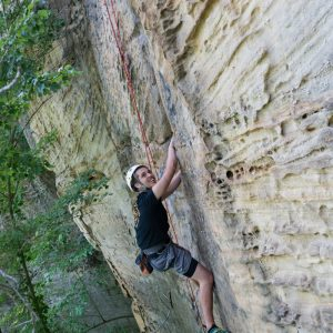 student climbing a cliff face