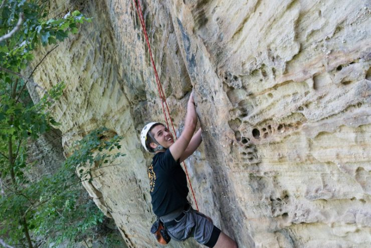 student climbing a cliff face