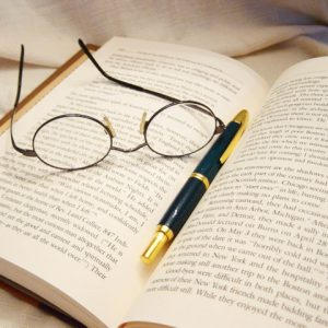 a pair of glasses and a pen on an open book