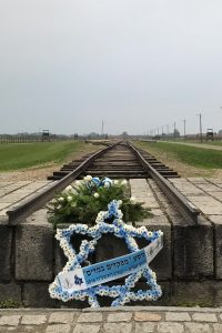 Cross of David and flowers by an old railroad track at a concentration camp