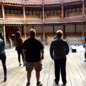 students walking on the stage of the Globe Theatre in London