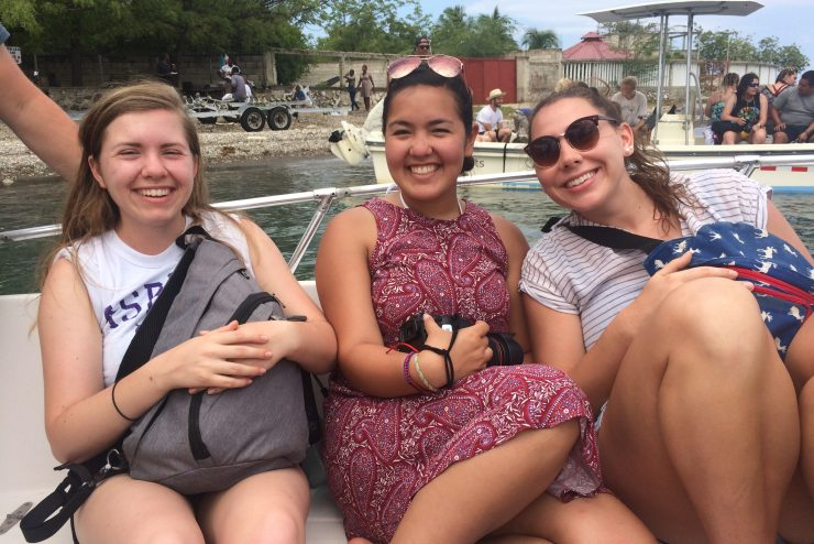 smiling students on a boat