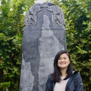 student standing in front of a large sculpture in China