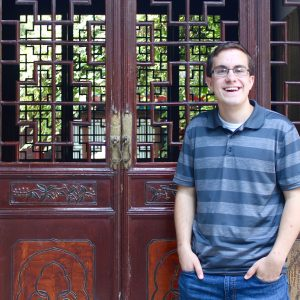 student in front of wooden doors in China