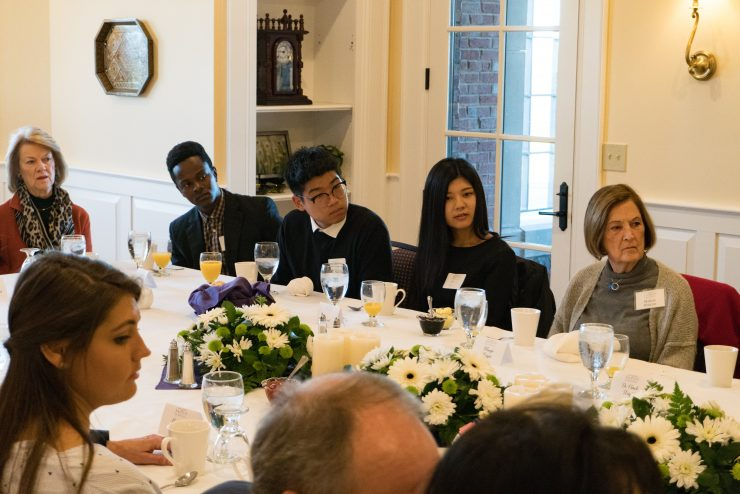 students, faculty, and administrators around a banquet table
