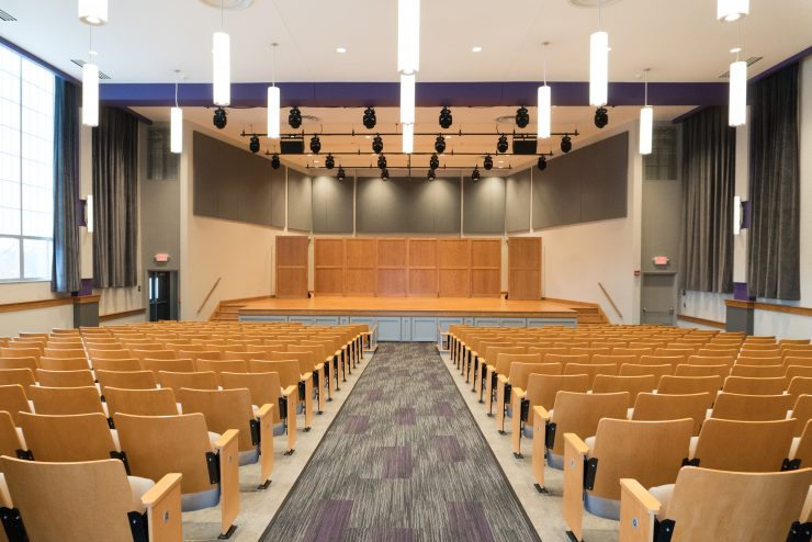 recital hall with seats, stage, and lighting