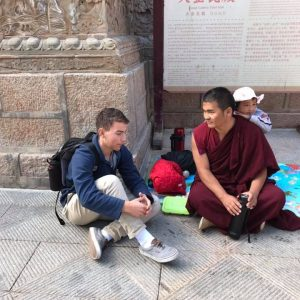 student conversing with a monk on a street in China