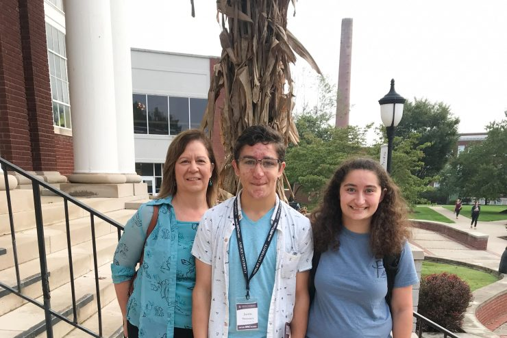 parent, student, and sibling standing on steps