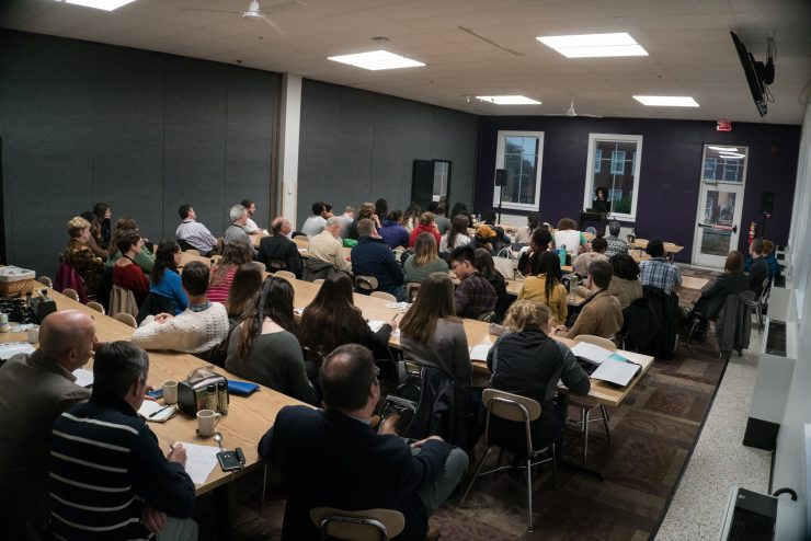 person speaking in a room to people seated at tables