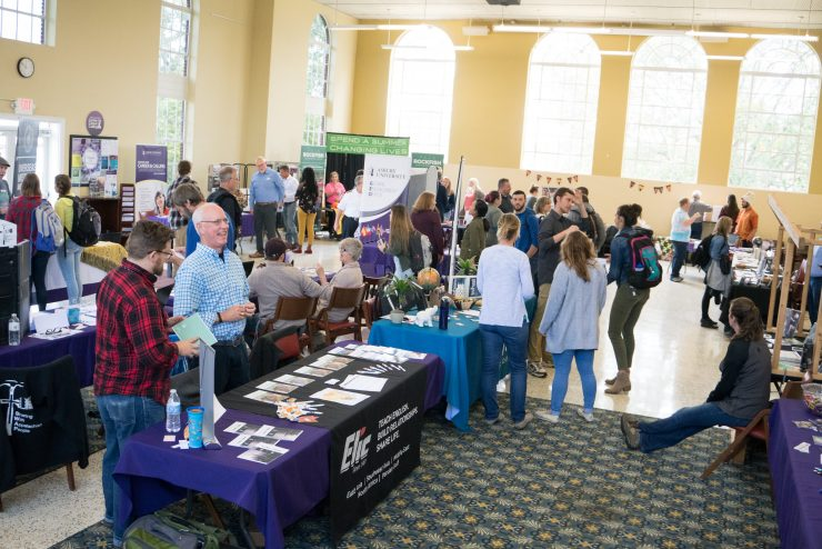 students standing and talking at a missions fair