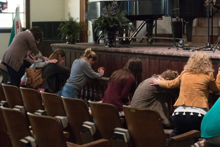 students praying at the altar in Hughes Auditorium