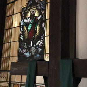 a cross next to a stained glass window