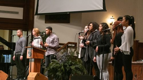 students singing on stage in chapel