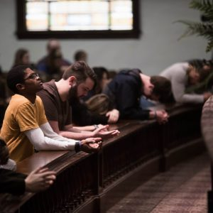 students praying in chapel