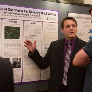 student giving a poster presentation of research