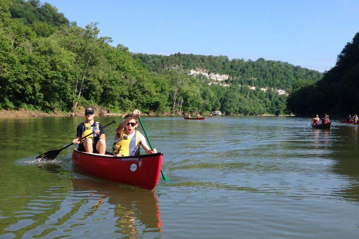 people paddling a canoe on a lake