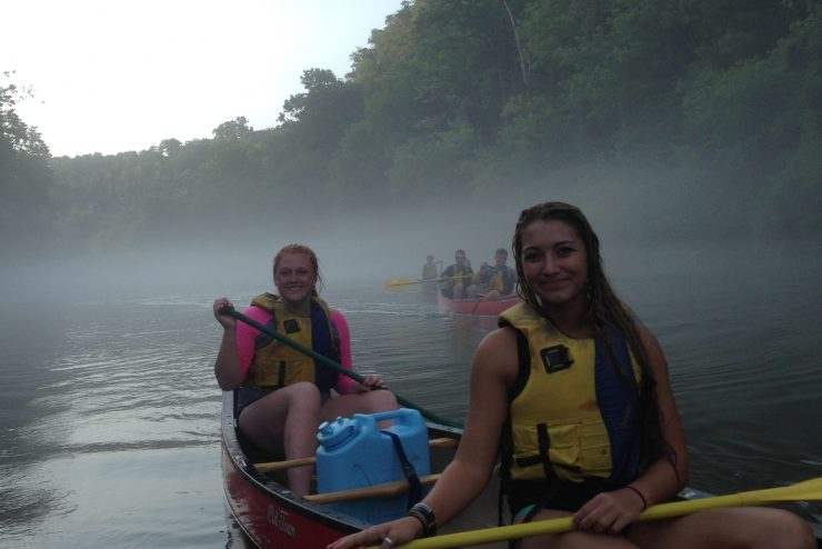 people in canoes on a foggy river