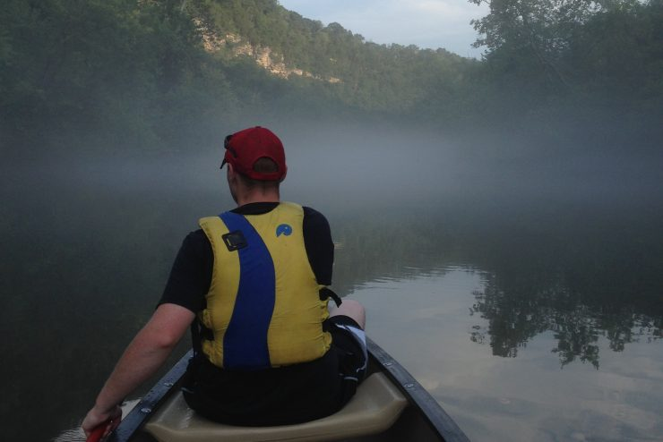 person paddling in the front of a canoe on a foggy river