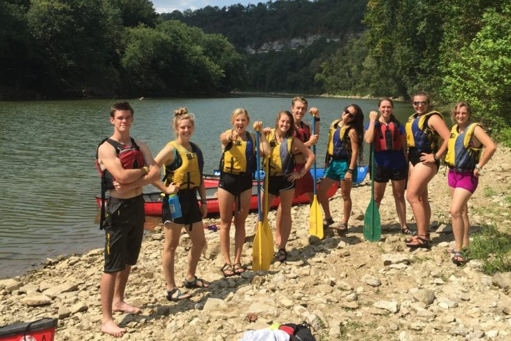 group photo of people in life jackets on a bank next to a river