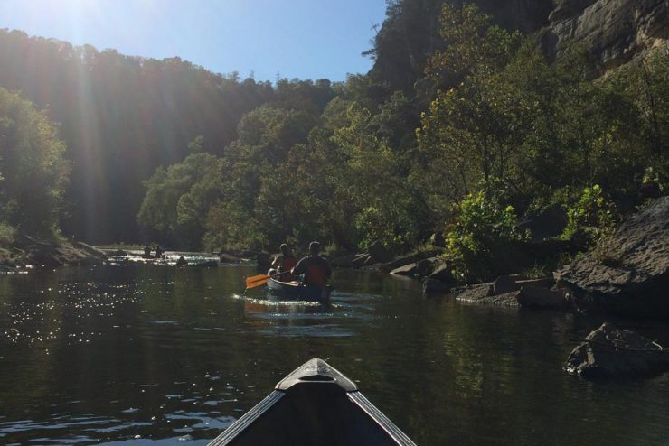 view from the front of a canoe on a river