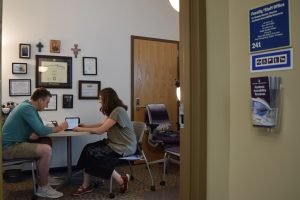 AAR Office, Kinlaw 241. Dr. Slocum and a student are sitting at a table in the office.