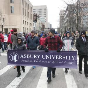 students carrying an Asbury University banner in a march