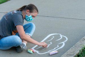 student drawing on a sidewalk
